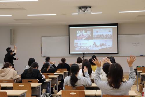 モニターの向こうにいる各大学の学生に手を振る本学の学生ら